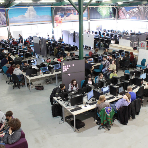 A large warehouse full of gaming students at computers and computer artwork on the walls