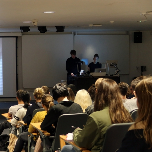 Students in lecture theatre, presentation by lecturer