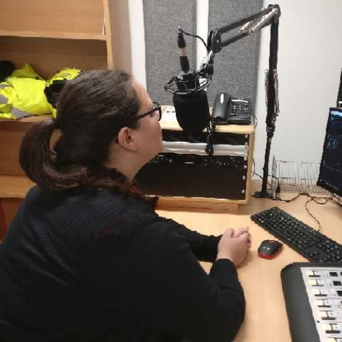 Woman sat at a desk taking into a microphone