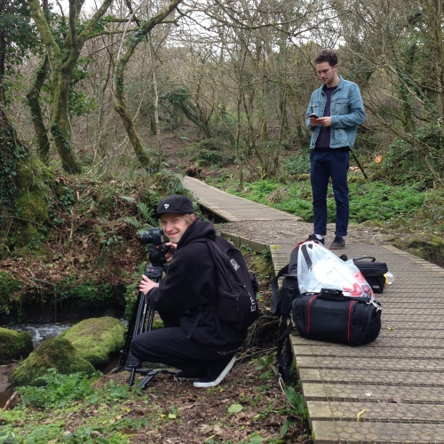 Students filming on location in woods with stream.