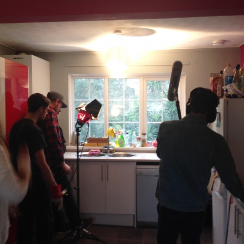 Students filming in kitchen.
