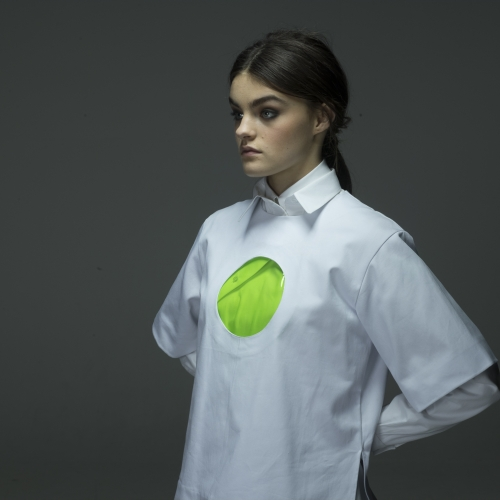 Model in white shirt that has a circular window revealing green fabric underneath.