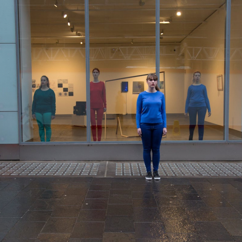 Performance art of women in a shop window and walking along the pavement