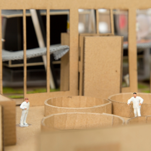 Cardboards mock up of interior with miniature figures of people in white suits.