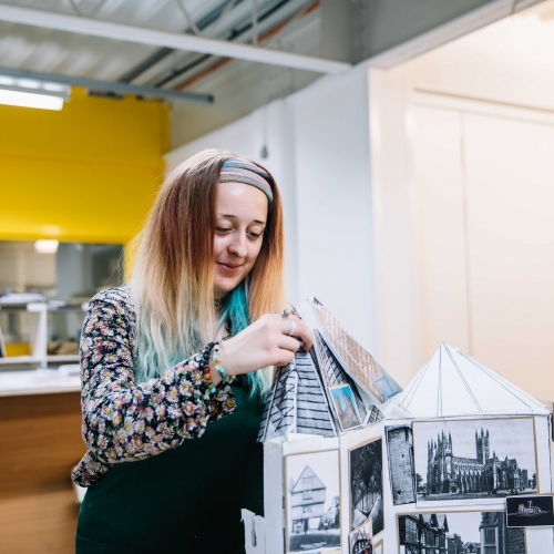 Interior design student fixing roof of cardboard model.
