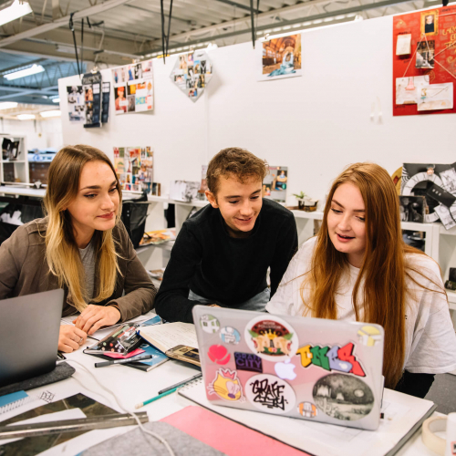 Students looking at a laptop together in design studio at Falmouth University