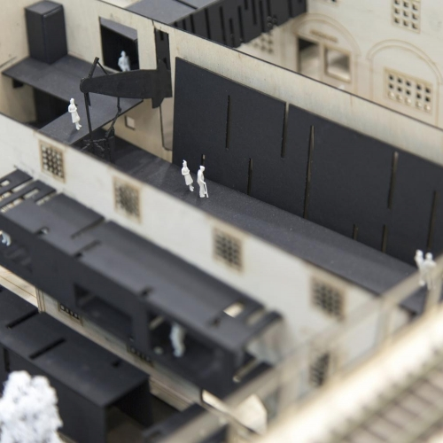Balsa wood mock up of building with walkways and sections in black and miniature white figures.