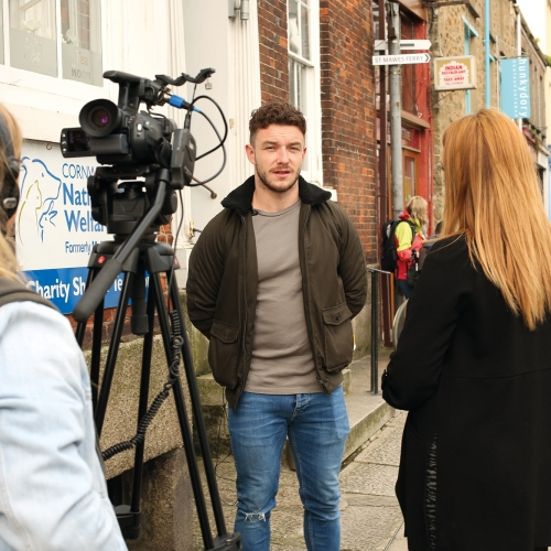 Students interviewing and filming on a street in Falmouth.