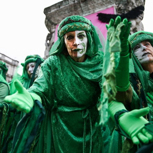 A crowd of people dressed in green robes with their faces painted