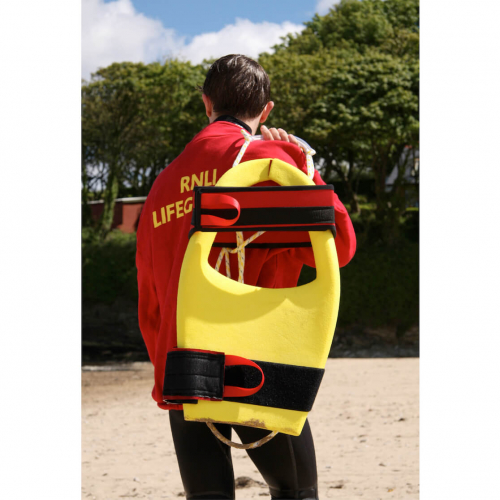 RNLI lifeguard carrying yellow float on back