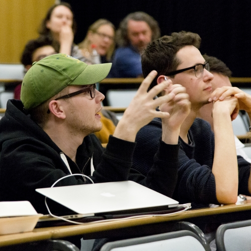 Student wearing green cap engaged discussion in lecture theatre.