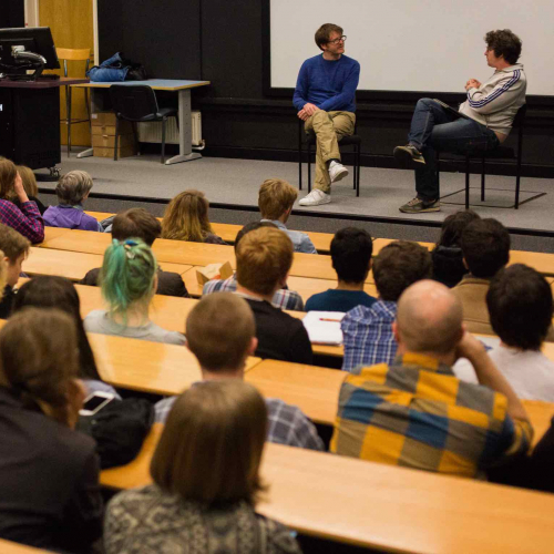 guest lecturer John Maclean on a stage with Film students sitting in an auditorium
