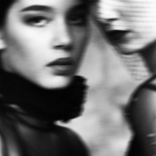 Out of focus cropped monochrome image of two models.