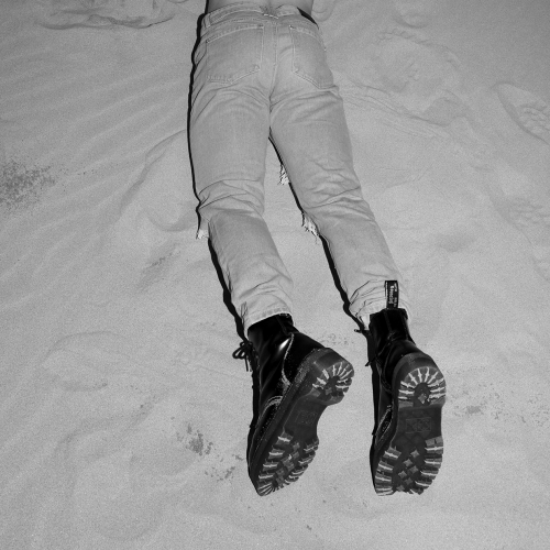 a man lying on his stomach int he sand, wearing light jeans and black boots