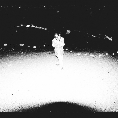 Grainy high contrast image of figure walking.