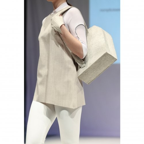 Model in white and cream outfit with matching gloves and bag.
