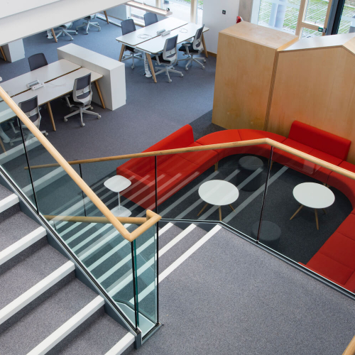 Looking down the staircase at Launchpad with a red sofa and desks