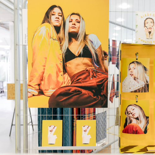 Exhibition of fashion photography featuring models on yellow background.