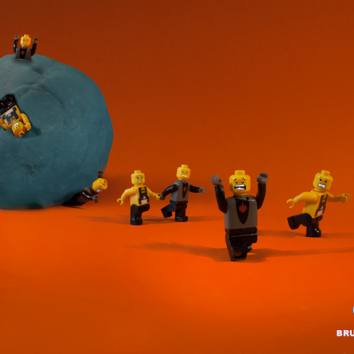 Lego figures being squashed by a ball of play-doh