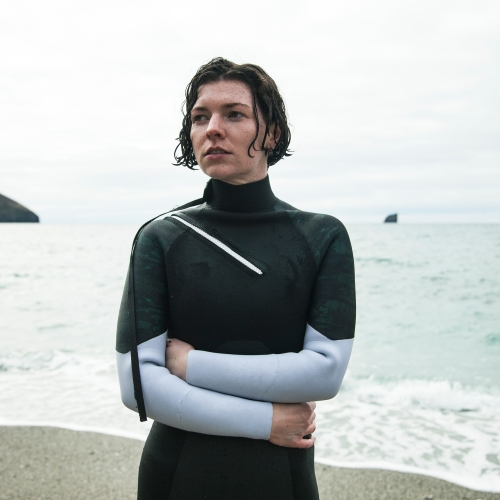 Model hugging herself after coming out of the sea in a dark green wetsuit with pale grey sleeves.