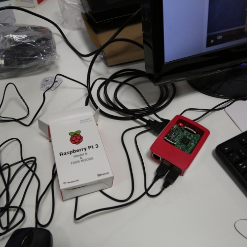 A small computer called a Raspberry Pi 3 on a a desk with wires and keyboard.