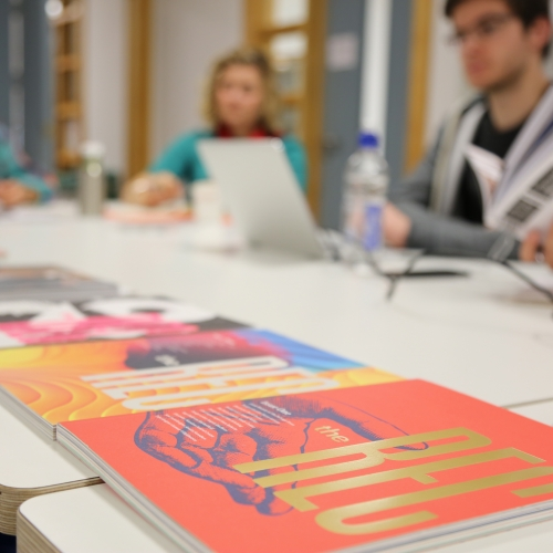 Design journals on a desk in the foreground, students working out of focus in the background.