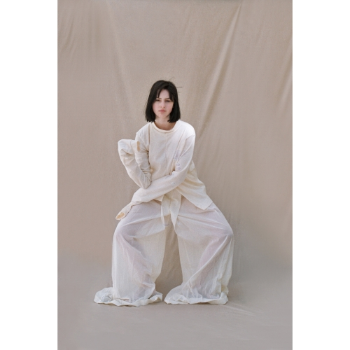 Model posing in simple, white baggy top and trousers.