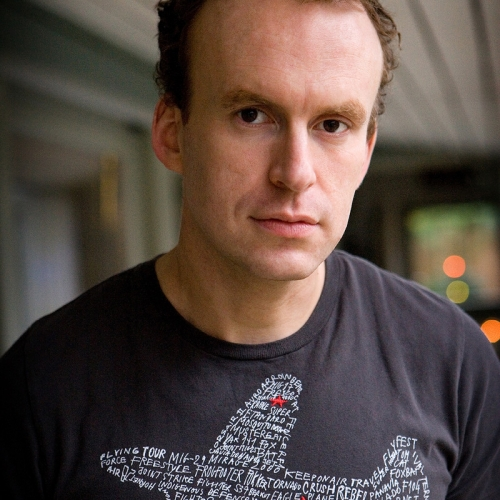 Portrait of writer, Matt Haig, with an aeroplane made of words on his t-shirt.