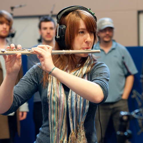 Girl with headphones on playing flute in recording studio.