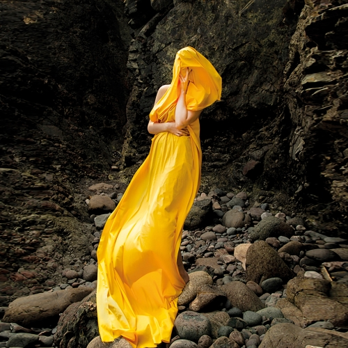 Model in yellow dress stood on rocks.