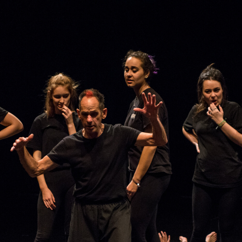 Student actors moving and wearing black on a black stage