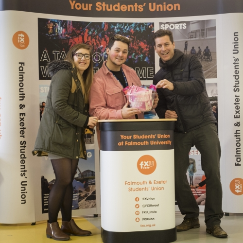 Students from the student union posing at their stand at an event.