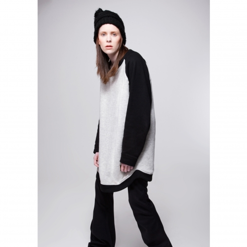 Model in black beanie hat and grey and black outfit.
