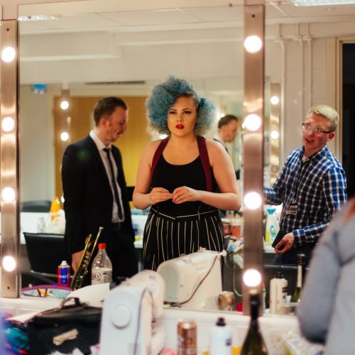 Backstage in the dressing room, actor with blue curly hair looking into mirror with lightbulbs.