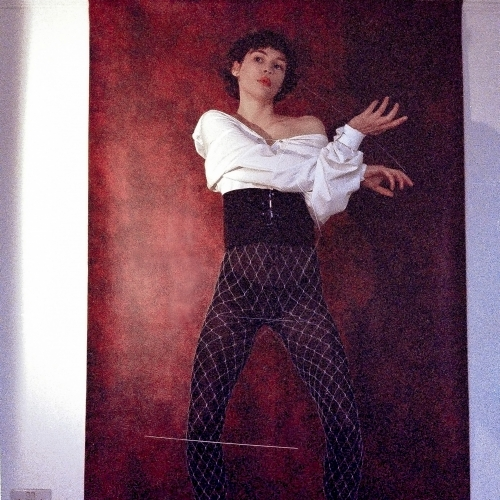 Model in black thick belt, white fish nets over black tights, red leatherette backdrop.