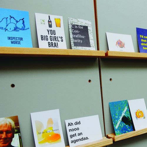 different card designs on shelves with a green wall