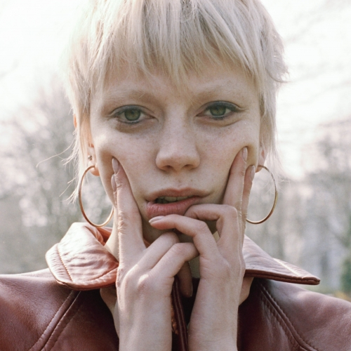 Model with blonde cropped hair pushing cheeks up with fingers and leather jacket.