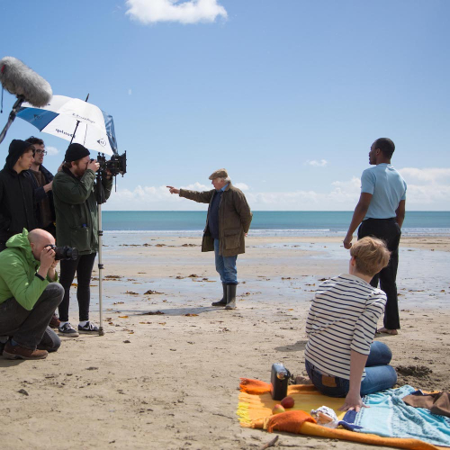 Film and TV students from Falmouth University filming a scene on a beach with blue sky