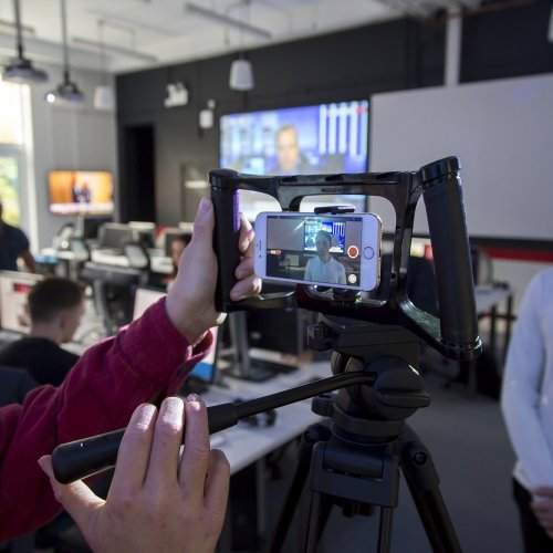 Student filming in the newsroom on smartphone.