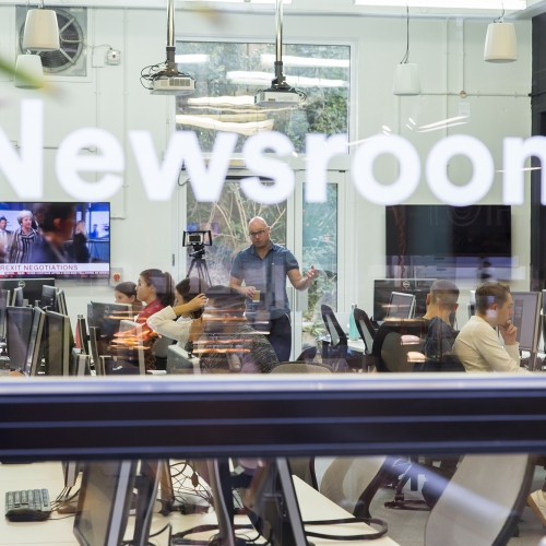 View through window into the newsroom.