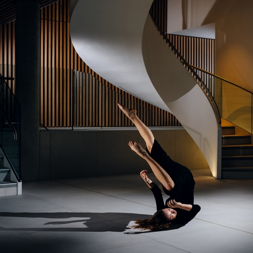 Woman in a black dress moving on the floor below a spiral staircase