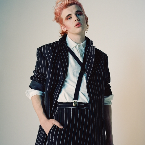 Model with pink hair in pinstripe suite and criss crossed braces.