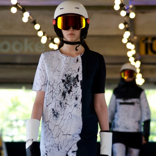 Model in white helmet and mirrored goggles walking the catwalk.