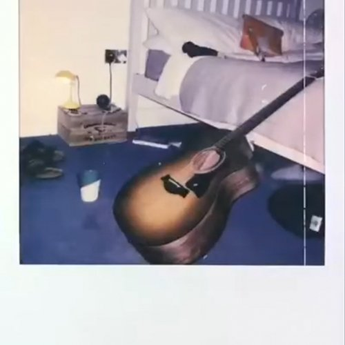 Guitar leaning on a bed