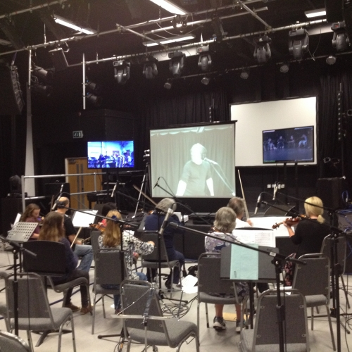 Group of musicians playing strings in front of a large screen