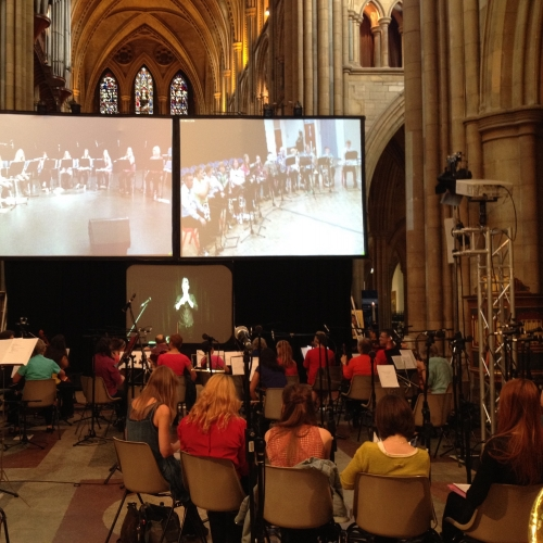 Group of people playing musical instruments in front of screens in a cathedral