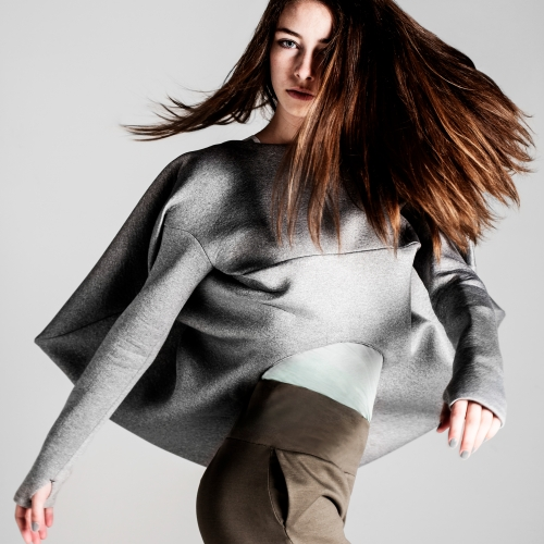Model swooshing hair in irregular shaped grey top.