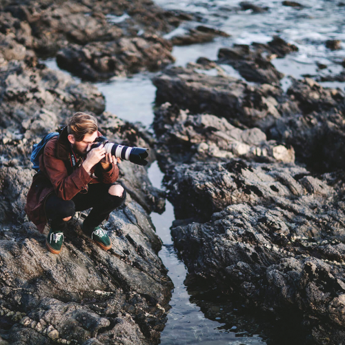 Falmouth University Photography student sits on rocks photographing the sea