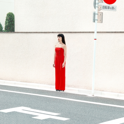 woman in a red dress standing at the edge of a road