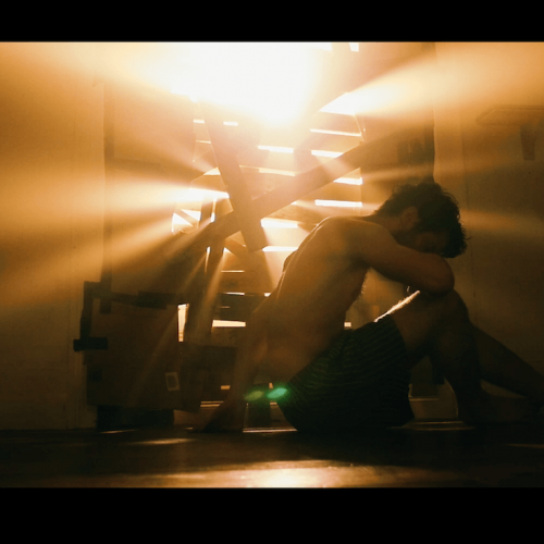 Film still of male in underwear with head in arms and light bursting through gaps in boarded up window.